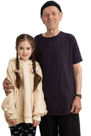Photo pour Attractive smiling old man in black hat, t-shirt and white wireless headphones, senior pencioner looking at the camera and hugging his granddaughter dressed in beige hoodie, white wall on the background - image libre de droit