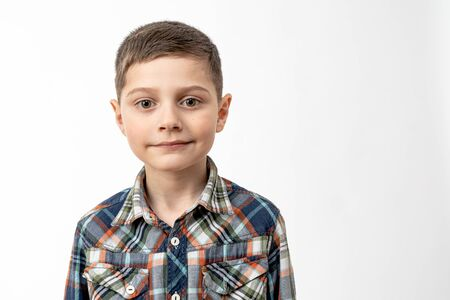 Photo for Close up portrait of the confident handsome little boy in shirt that looking at the camera isolated over white background, copyspace for your text - Royalty Free Image