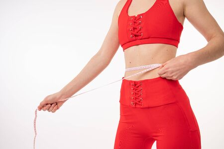 Photo pour Beautiful young woman in red sportswear with measuring tape on white background. Weight loss concept - image libre de droit