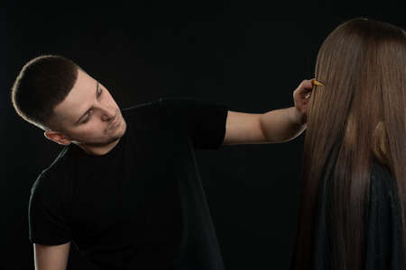 Attractive young Hair Dresser Combing Clients Hair In Salon