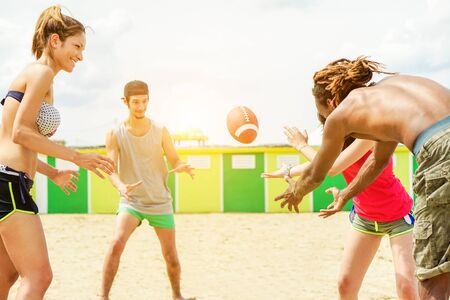 Happy friends playing rugby on sand beach with back sun light - Young people having fun with sport summer games - Holidays and friendship concept - Focus on left woman,ball - Warm filter
