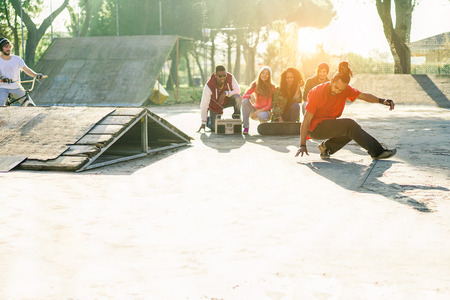 Group of happy friends listening music and watching breakdancer perfoming in city skate park - Young people having fun - Hip hop lifestyle concept - Focus on man dancing - Warm filter with sunlight