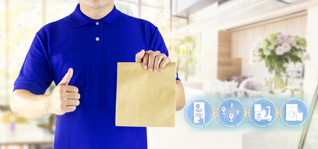 Foto de Delivery man hand holding paper bag in blue uniform and icon media for delivering package order online fast food delivery service by motorcycle or express delivery on coffee shop background. - Imagen libre de derechos