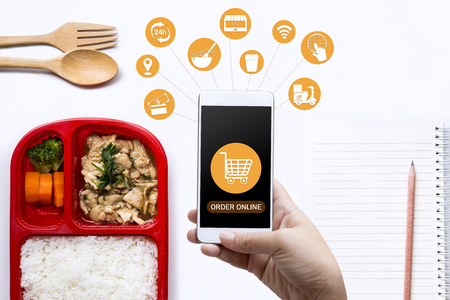 Foto de Food delivery service for order online and icon media. Woman hand holding smart phone for ordering food onscreen. Business and technology for shopping online with lifestyle in city concept. - Imagen libre de derechos