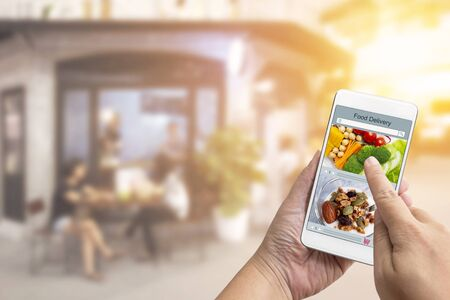 Foto de Online order Food shopping concept on touch screen on woman hand. Food delivery service express that is cooked by restaurant and icon symbol media. Business and technology with lifestyle in city. - Imagen libre de derechos