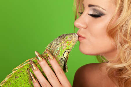 Portrait of a young woman with beautiful manicure kissing a iguana