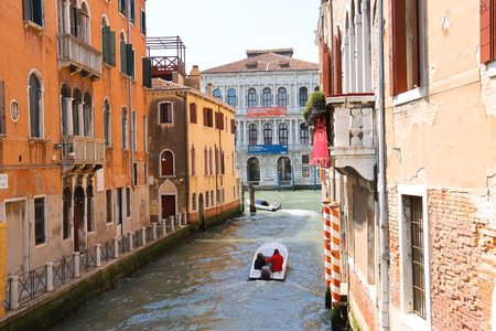 VENICE, ITALY - MAY 06, 2014: People move through the channel on the boat in Venice, Italy