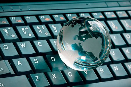 small glass globe on a laptop keyboard