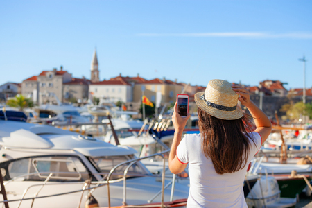Photo for Young travelling woman in hat taking photos of summer sunny Budva landscape with smartphone camera. Brunette girl making photography on summer mediterranean destination in Montenegro - Royalty Free Image