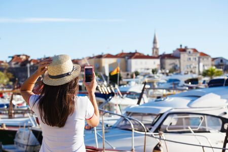 Photo for Young travelling woman in hat taking photos of summer sunny sea with smartphone camera. Brunette girl making photography on summer vacation - Royalty Free Image