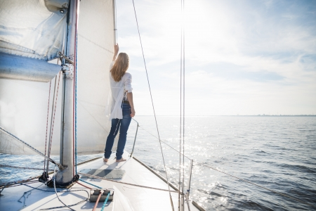 woman staying on the sailboat during sunset