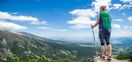 Photo for Young woman with backpack hiking in the mountains - Royalty Free Image