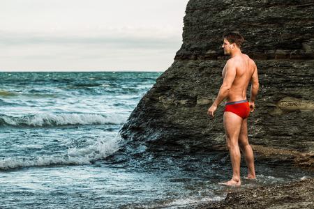 Muscular man on a beach in underwear.