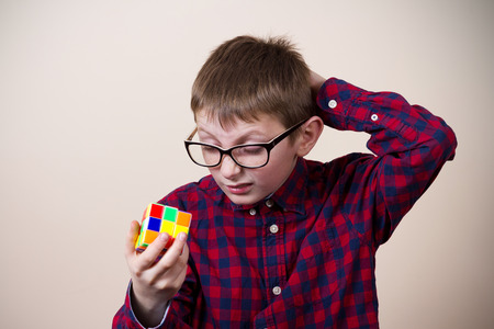 Confused little boy nerd, holding a puzzle cube and a hand on his head.Concept, perplexed.