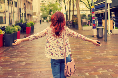 Photo for Freedom-Young woman with raised hands in a city.Young woman walking with raised hands feeling free.Life style - Royalty Free Image