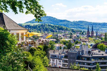 Foto de Aerial view on church, city of Freiburg im Breisgau, Beer garden, Schwarzwald mountains. Baden-Württemberg, Germany. - Imagen libre de derechos