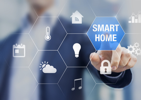 Foto de Smart home automation concept with icons showing the functionalities of this new technology and a person touching a button - Imagen libre de derechos