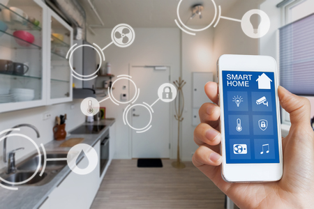 Foto de Smart home interface on smartphone app screen with augmented reality (AR) view of internet of things (IOT) connected objects in the appartment interior, person holding device - Imagen libre de derechos