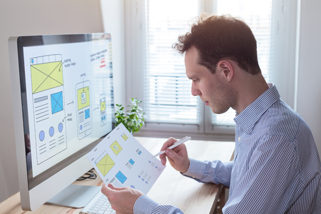 Foto de Website UI/UX front end designer reading client specification document and sketching wireframe layout design for responsive web content - Imagen libre de derechos