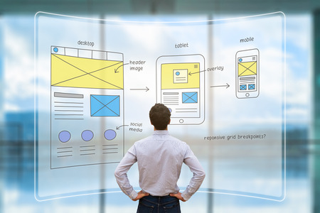 Photo pour Website development UI/UX front end designer reviewing sketched wireframe layout design mockup for responsive web content with AR screen - image libre de droit