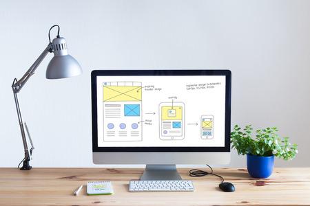 Foto de Responsive web design development technology concept with desktop computer in modern bright office and website wireframe sketch layout on screen, nobody - Imagen libre de derechos