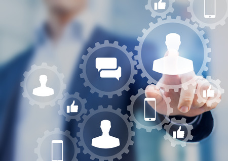 Foto de Social media digital marketing concept with icons of people profile, like, comment and smartphone inside connected gears network, businessman in background - Imagen libre de derechos