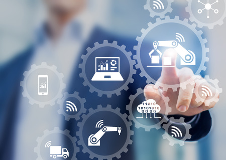Foto de Smart factory and industry 4.0 concept with connected production robots exchanging data with internet of things (IoT) and cloud computing technology, businessman touching interface with icons in gears - Imagen libre de derechos