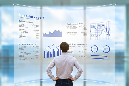 Foto de Businessman analyzing financial report data of the company operations (balance sheet, income statement) on virtual computer screen with business charts, fintech - Imagen libre de derechos
