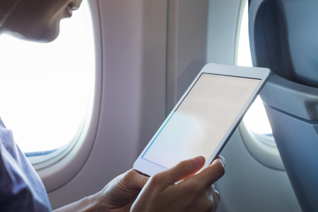 Photo pour Passenger using tablet computer in airplane cabin during flight with wireless internet to read emails or an ebook, hands holding device with white empty screen for copy-space, onboard entertainment - image libre de droit
