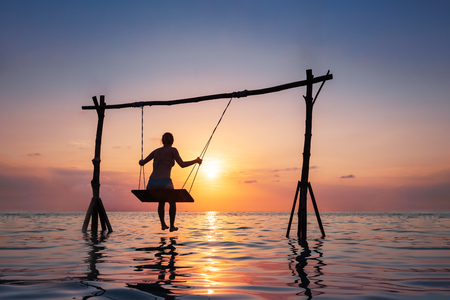 Photo for Happy girl relaxing at the beach on rope swing above sea water at sunset, summer vacation holidays resort - Royalty Free Image
