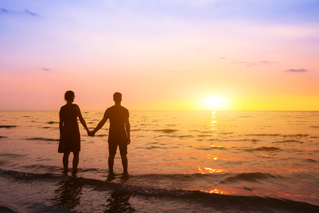 Photo pour Romantic couple on the beach at sunset watching horizon, honeymoon vacation holidays at sea destination, silhouette of two lovers holding hand - image libre de droit