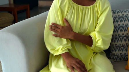 Photo pour A young girl touches a yellow dress sitting on a couch in the house with her hand - image libre de droit
