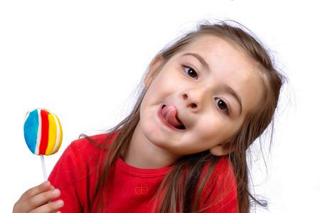 Photo pour Portrait of little girl eating a colorful lollipop on studio. - image libre de droit