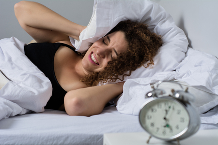 Photo pour Young woman with pillow over her head hates waking up early in the morning. - image libre de droit