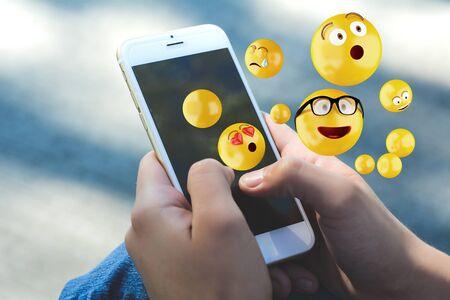 Foto de Close-up of woman using smartphone sending emojis. Social concept. - Imagen libre de derechos