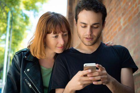 Photo pour Young couple having fun using application on smartphone outdoors. - image libre de droit