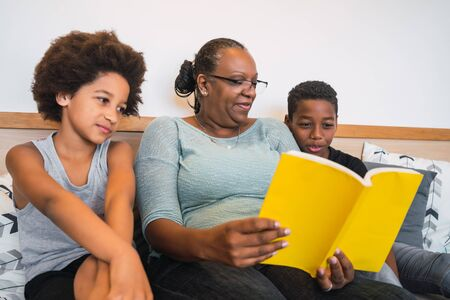 Photo pour Portrait of African American grandmother reading a book to her grandchildren at home. Family concept. - image libre de droit