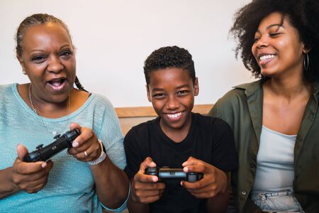Photo pour Portrait of African American grandmother, mother and son playing video games together at home. Technology and lifestyle concept. - image libre de droit