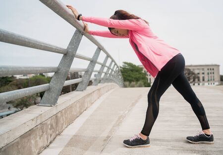 Foto für Portrait of an athletic woman stretching legs before exercise outdoors. Sport and healthy lifestyle. - Lizenzfreies Bild