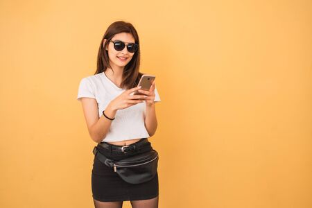 Portrait of young woman wearing summer clothes and using her mobile phone against yellow background. Urban and communication concept.