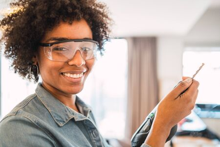 Photo pour Portrait of young afro woman drilling wall with an electric drill at home. Home improvement concept. - image libre de droit