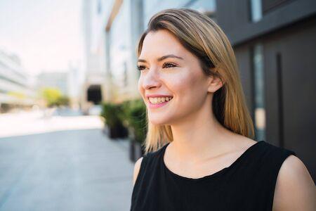 Photo pour Portrait of young business woman standing outside office buildings. Business and success concept. - image libre de droit