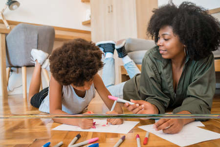 Foto de Portrait of young african american mother and son drawing with colored pencils on warm floor at home. Family concept. - Imagen libre de derechos