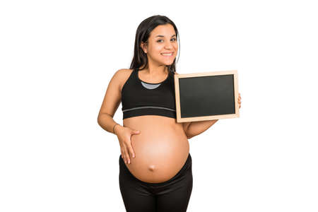 Photo pour Close-up of pregnant woman holding and showing something on chalkboard. Pregnancy, motherhood and promotion ad concept. - image libre de droit