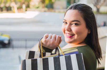 Photo pour Young woman holding shopping bags at mall. - image libre de droit