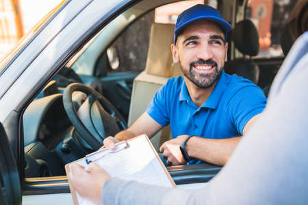 Photo pour Delivery man in van while customer sign in clipboard. - image libre de droit