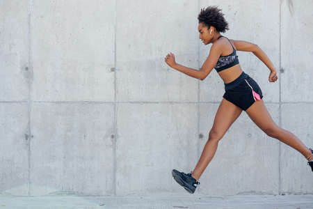 Photo for Afro athletic woman running outdoors. - Royalty Free Image