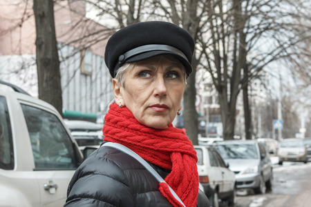 pretty and serious middle-aged lady in a red scarf, cap, earrings and black jacket against the background of the city. closeup portrait of elegant middle aged woman. Lovely middle-aged gray-haired woman with a serious face. serious middle-aged woman with