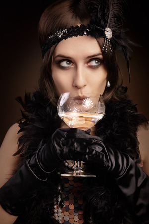 Portrait of a flapper girl at a party drinking champagne