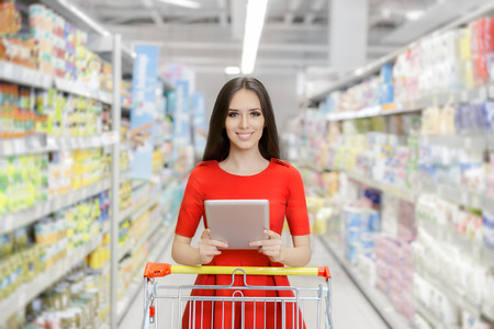 Happy Woman with Tablet Shopping  at The Supermarket